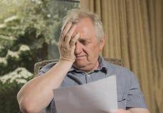 Dorośleć mężczyzna patrzeje zaakcentowanego czytanie list Obraz Royalty Free