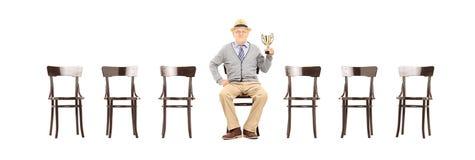 Dorośleć mężczyzna trzyma trofeum sadzający na drewnianym krześle Fotografia Royalty Free