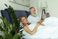 Dorośleć mężczyzna używa laptop w łóżku podczas gdy blondynki kobiety dosypianie Obrazy Royalty Free