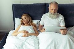 Dorośleć mężczyzna używa laptop w łóżku podczas gdy blondynki kobiety dosypianie Zdjęcie Royalty Free
