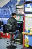 Dorośleć mężczyzna używa niezmiennych szanse Ruletową maszynę w bukmacherach england London uk Maszyna opisująca jako crack obrazy stock