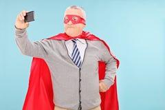 Dorośleć mężczyzna w bohatera kostiumowym bierze selfie Fotografia Royalty Free