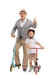 Dorośleć mężczyzna z hulajnoga daje kciukowi i chłopiec z sco up Zdjęcia Stock