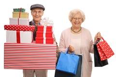 Dorośleć mężczyzna z teraźniejszość i dorośleć kobiety z torba na zakupy Zdjęcia Royalty Free