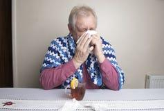 Dorośleć mężczyzna z zimnym kichnięciem i pić gorącej herbaty obrazy royalty free