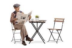 Dorośleć mężczyzny czyta gazetę przy stolikiem do kawy obraz stock