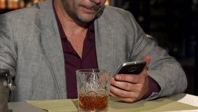 Dorośleć mężczyzny używa mądrze telefon podczas gdy dodający kostka lodu jego whisky zdjęcie wideo
