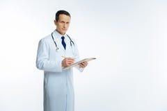 Dorośleć medycznego pracownika pozuje podczas gdy robić notatce Obrazy Stock