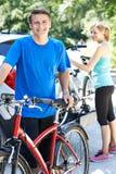 Dorośleć pary Bierze rowery górskich Od stojaka Na samochodzie obraz royalty free