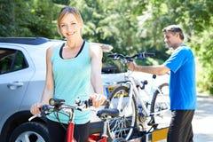 Dorośleć pary Bierze rowery górskich Od stojaka Na samochodzie obrazy royalty free