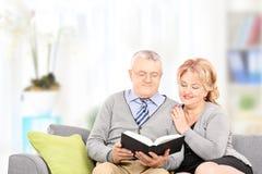 Dorośleć pary czyta książkę sadzającą na leżance Obraz Royalty Free