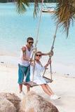 Dorośleć pary na wakacje przy plażą, kobieta na huśtawce Zdjęcie Stock
