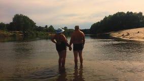 Dorośleć pary -- obejmuje przegapiać rzekę Piękna para seniory blisko nawadnia Starzy szczęśliwi ludzie trzyma ręki zbiory