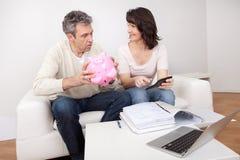 Dorośleć pary oszczędzania pieniądze w piggybank zdjęcie stock