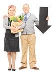 Dorośleć pary trzyma papierową torbę dużego czarnego strzałkowatego wskazuje d i Obraz Stock
