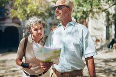 Dorośleć pary używa mapę na wakacje Fotografia Stock