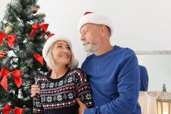 Dorośleć pary w Santa kapeluszach w domu fotografia stock