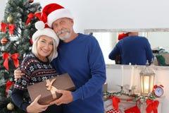 Dorośleć pary w Santa kapeluszach z Bożenarodzeniowym prezenta pudełkiem zdjęcie royalty free