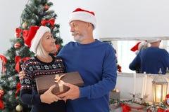 Dorośleć pary w Santa kapeluszach z Bożenarodzeniowym prezenta pudełkiem zdjęcie stock