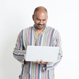 Dorośleć przypadkowego Indiańskiego mężczyzna używa laptop Fotografia Royalty Free
