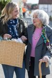 Dorośleć Sąsiedniej Pomaga Starszej kobiety Nieść zakupy obraz stock