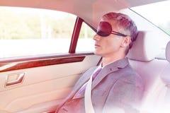 Doro?le? biznesmena drzemanie podczas gdy b?d?cy ubranym oko mask? w samochodzie obrazy stock