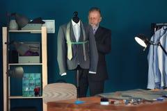 Doro?le? krawczyny bierze pomiary kurtka na mannequin w atelier obrazy stock