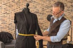Doro?le? krawczyny bierze pomiary kurtka na mannequin w atelier zdjęcia stock