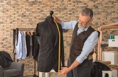 Doro?le? krawczyny bierze pomiary kurtka na mannequin w atelier obraz royalty free
