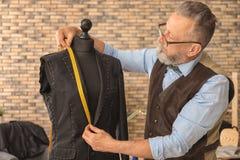 Doro?le? krawczyny bierze pomiary kurtka na mannequin w atelier zdjęcia royalty free