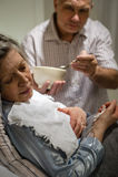 Dorośleć mężczyzna pomaga chorej żony żywieniowej polewce Zdjęcia Stock