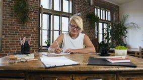 Dorosła atrakcyjna dama nagrywa coś w notatniku podczas gdy pracujący w ministerstwo spraw wewnętrznych obsiadaniu za biurkiem zdjęcie wideo
