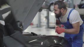 Dorosła mechanik pozycja blisko samochodu z otwartym kapiszonem i weryfikuje warunek silnik Brodaty mężczyzna w mundurze i zbiory wideo