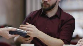 Dorosły mężczyzny obsiadanie z jego dziewczyną w restauracji i płacić rachunek używać smartphone zapłatę zbiory wideo