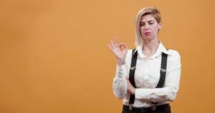 Dorosła blondynki kobieta zatwierdza akcję i pokazuje ok znaka zbiory
