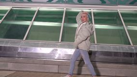 Dorosła dziewczyna z krótkim farbującym blondynka włosy odprowadzeniem wzdłuż ulicy przy nocą, jest ubranym białą kurtkę, rozdzie zdjęcie wideo