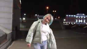 Dorosła dziewczyna z krótkim farbującym blondynka włosy odprowadzeniem wzdłuż ulicy przy nocą, jest ubranym białą kurtkę, rozdzie zbiory wideo