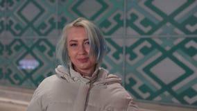 Dorosła dziewczyna z krótkim farbującym blondynka włosy odprowadzeniem wzdłuż ulicy przy nocą, jest ubranym białą kurtkę, rozdzie zbiory