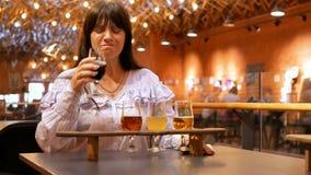 Dorosła kobieta kosztuje kilka typ piwo w małych szkłach na drewnianym stojaku Degustator no polubił napoju bardzo mocno zbiory