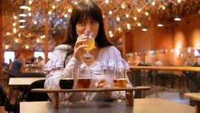 Dorosła kobieta kosztuje kilka typ piwo w małych szkłach na drewnianym stojaku Degustator no polubił napoju bardzo mocno zbiory wideo