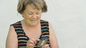 Dorosła kobieta opowiada z mężem używa mądrze telefon zbiory wideo