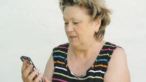 Dorosła kobieta opowiada z mężem używa mądrze telefon zbiory