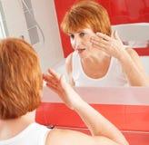 Dorosła kobieta patrzeje lustro zdjęcia stock