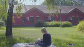 Dorosła kobieta relaksuje na koc używa cyfrową pastylkę w parku zbiory