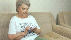 Dorosła kobieta trzyma telefon komórkowego w domu zbiory