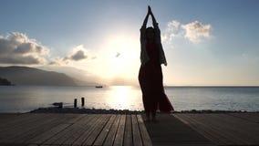 Dorosła kobieta uprawiająca duchowe praktyki w pobliżu morza przy wschodzie słońca w zwolnionym tempie zbiory wideo