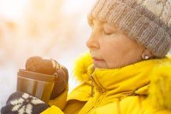 Dorosła kobieta w żółtej zimy kurtce cieszy się kawę na zima dniu fotografia royalty free