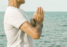 Dorosła mężczyzna pozycja z palmami w gesta namaste morzem Pojęcie duchowość i świadomość zdjęcie royalty free
