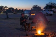 Dorosła para relaksuje w campingowym miejscu nocą Przygoda w parku narodowym, Południowa Afryka Płonący obozu ogień, namiot w bac Obraz Royalty Free