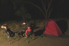 Dorosła para relaksuje w campingowym miejscu nocą Przygoda w parku narodowym, Południowa Afryka Płonący obozu ogień, namiot w bac Obrazy Royalty Free